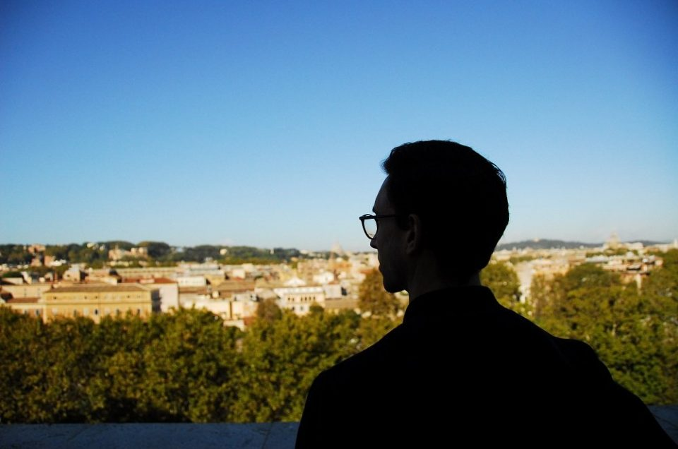 Traveller looking out over Rome and the Vatican from the Orange Garden on the Aventine Hill