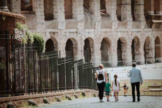Family on a tour walking down the Via Sacra towards the Colosseum