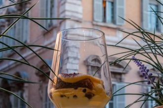 Tiramisù in a glass cup against Palazzo Madama in Rome's historic centre