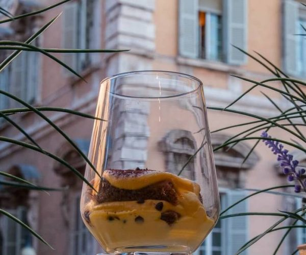 Tiramisù in a glass cup against Palazzo Madama in Rome's historic centre
